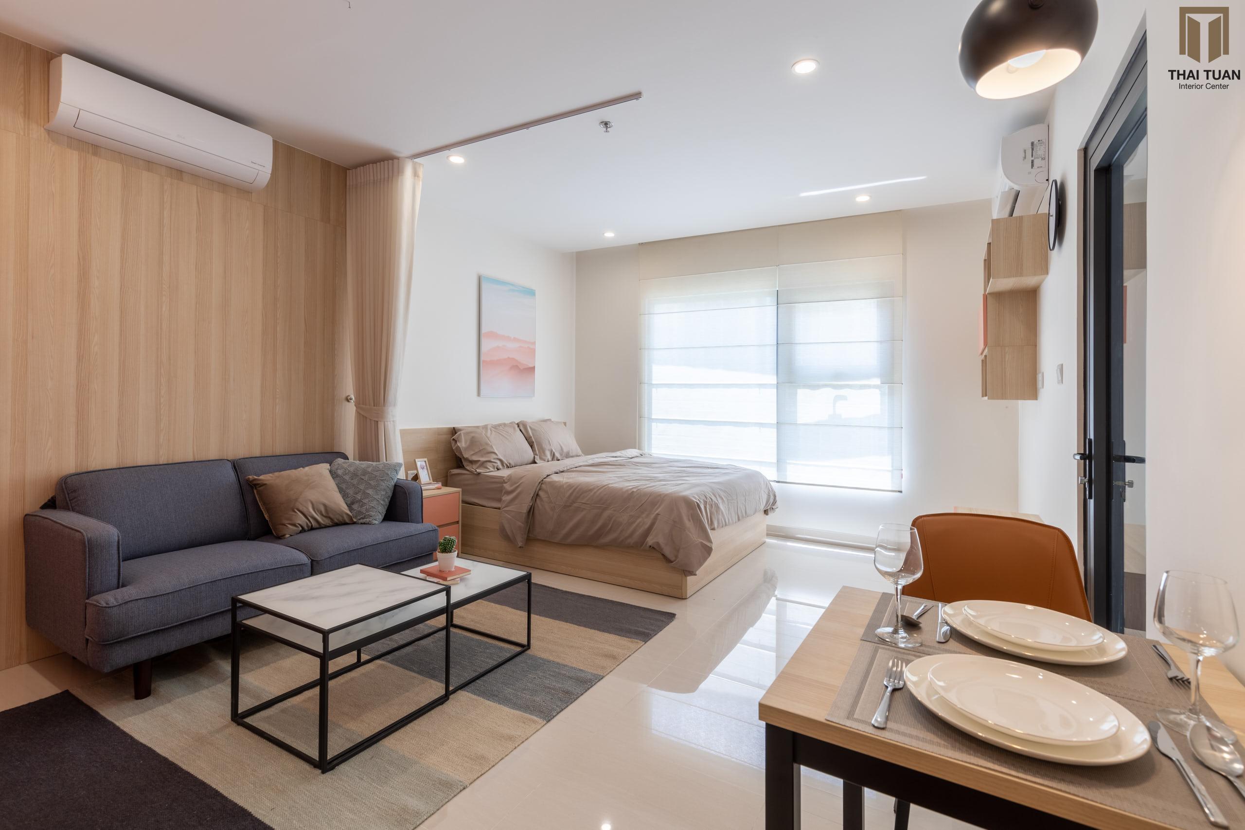 Phòng khách được ngăn cách với phòng ngủ bởi rèm thả, tạo sự riêng tư